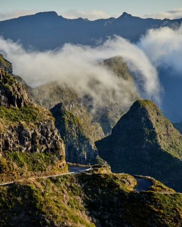 Clouds crest over a distant mountain ridge.     Size: 4480 x 5600