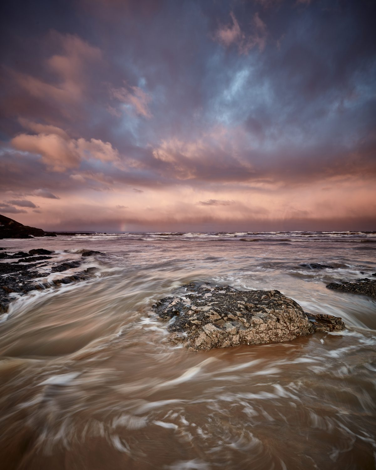 Water swirls over rocks on a beach under a stormy red sky